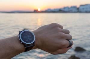 Garmin-Sportuhr am Handgelenk eines Mannes, vor dem Mittelmeer und Sonnenuntergang am Horizont