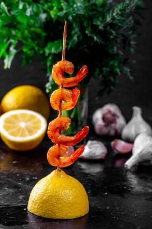 Garnelen kreativ angerichtet auf einem Holzspieß, über einer Zitronenhälfte, mit Kräuter und Knoblauch im Hintergrund