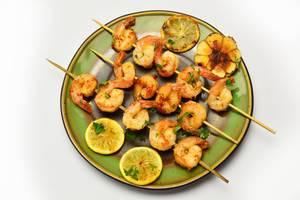 Garnelen-Spieße mit Zitrone auf einem Teller in der Aufsicht