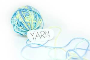 Garnkugel in Pastellfarben und Papier mit Schriftzug YARN vor weißem Hintergrund