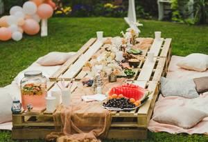 Gartenmöbel aus Holzpaletten: gedeckter Dessert Lily Party-Tisch mit frischem Obst und Decken auf dem Rasen