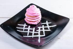 Gebäck mit pinker Sahne auf schwarzem Teller