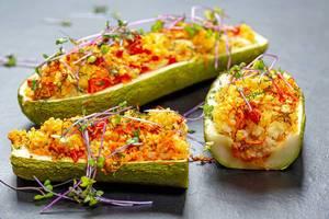 Gebackene, gefüllte Zucchini mit Gemüse, Couscous und Keimsaat auf einem schwarzen Tisch