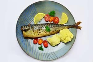 Gebackene Makrele mit Blumenkohl und Kirschtomaten auf einem Teller mit Zitronenscheiben