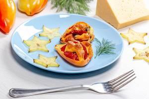 Gebackene Paprika mit Tomaten und Käse, neben Sternfrucht