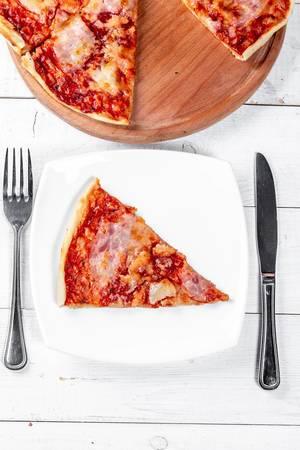 Gebackene Pizza auf einem runden Holzbrettchen und ein einzelnes Stück, auf einem weißen Teller