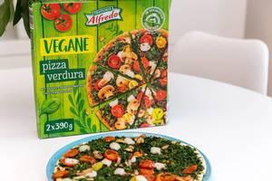 Gebackene Pizza Verdura von Trattoria Alfredo, mit Spinatbelag, Champignons und Cherrytomaten vor dem Pizzakarton auf einem weißen Tisch