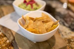 Gebackene Tortilla Chips mit Guacamole in weißen Schalen auf einem Holzbrett serviert, im Fit Kitchen in Barcelona Spanien