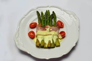 Gebackener grüner Spargel mit Schinken und Sauce Hollandaise mit Kirschtomaten auf einem Teller