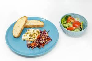Gebackener Hirtenkäse an Tomatengemüse dazu Knoblauchfladenbrot auf einem blauen Teller und ein frischer Salat auf weißem Hintergrund