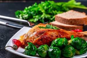 Gebackenes Hühnerbein mit Rosenkohl auf einem Teller & Brot und Petersilie im Hintergrund