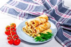Gebratene Eierkuchen, gestapelt neben einem Tomatenstrang und einem Abtrockentuch