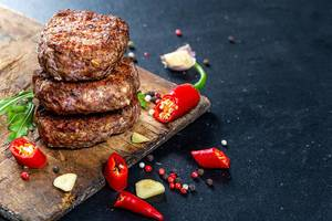 Gebratene Fleischkoteletts mit Knoblauch, geschnittener Chilischote, Pfefferkörnern und Kräutern auf einem alten Küchenbrettchen