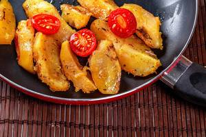 Gebratene Kartoffeln in einer Pfanne mit Kirschtomaten