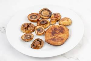 Gebratene Pilze neben einem Stück Schweinekotelett auf einem Teller auf der Küchentheke