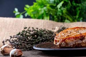 Gebratenes Fleisch auf braunem Teller mit Knoblauch und Kräutern auf einem Holztisch