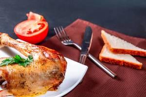 Gebratenes Hühnerbein auf einem Teller mit Besteck
