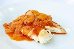 Gebratenes Hühnerfleisch mit Tomatensauce auf einem Teller