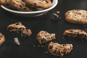 Gebrochene Kekse mit Schokoladenstückchen auf schwarzem Hintergrund