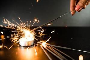 Geburtstags-Wunderkerze sprüht helle Funken zum Fest, über einem kleinen Teelicht auf einem schwarzen Tisch