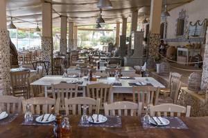 Gedeckte Tische mit Platzdeckchen in einem schicken Restaurant mit Meerblick