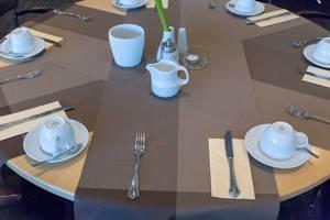 Gedeckter Tisch mit Kaffeetassen und Besteck
