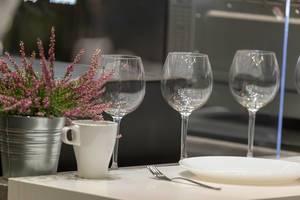 Gedeckter Tisch mit Weingläsern und einer Topfpflanze im Blecheimer