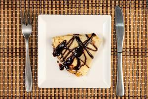 Gefalteter, dreieckiger Pfannkuchen mit Schokolade überzogen auf weißem Teller