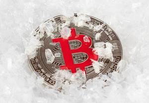Gefrorene Bitcoin Münze auf Schneeflocken