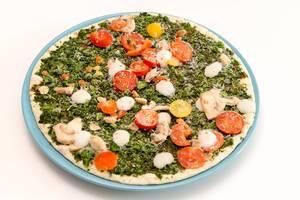 Gefrorene, vegane Fertigpizza Verdura der Trattoria Alfredo, mit Spinat, Cherrytomaten und Champignons vor weißem Hintergrund