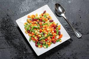 Gefrorenes buntes Gemüse auf einem weißen Teller und schwarzen Hintergrund - Top-view