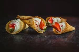 Gefüllte Eiscreme-Waffeln mit Sahne und Erdbeer-Viertel in Nahansicht
