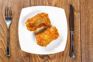 Gefülltes Schmorrgericht mit Tomatensoße, auf einem Teller neben Besteck, auf einem dunklen Holztisch