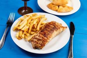 Gefülltes Schweinefleisch mit Pommes Frites angerichtet auf weißem Teller, mit Besteck auf blauem Holztisch
