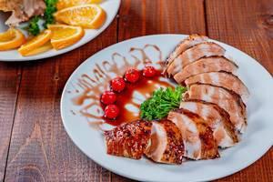 Gegrillte Hähnchenbrust in Scheiben mit Granatapfelsoße auf einem Teller mit gegrillten Kirschtomaten und Petersilie