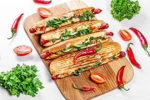 Gegrillte Hotdogs mit frischem Gemüse, Kräutern und Chili-Schoten