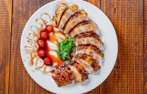 Gegrillte Hühnerbrust mit Granatapfelsoße auf einem Teller mit Tomaten - Aufsicht