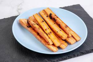 Gegrillte Karottensticks auf einer schwarzen Schiefersteinplatte