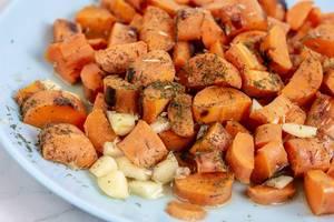Gegrillte Karottenstücke mit Kräutern und Knoblauch serviert