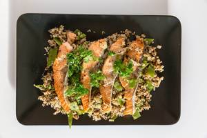 Gegrillte Lachsscheiben auf Blumenkohl-Quinova mit Parmesanchips auf schwarzem Teller