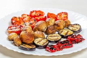 Gegrillte Tomaten, Paprika, Pilze und Auberginen, auf einem weißen Teller
