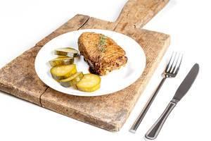 Gegrillter Kebab mit geschnittenen Gewürzgurken und Kräuter, neben Besteck auf einem rustikalen Holzbrettchen