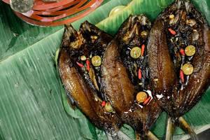 Gegrillter Milchfisch wird auf Bananenblättern serviert