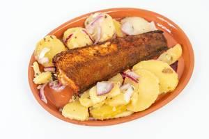 Gegrillter Seehecht und Kartoffelsalat auf einem Teller vor weißem Hintergrund