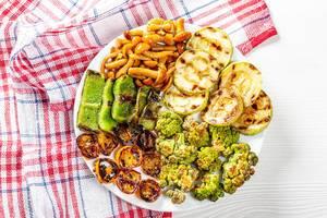 Gegrilltes Gemüse und eingelegte Pilze auf einem weißen Teller, neben einem roten Geschirrtuch