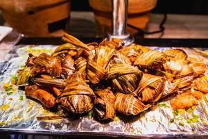 Gegrilltes Hähnchenfleisch, in Blätter gewickelt, an einem asiatischen Büfett