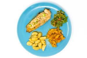 Gegrilltes Lachssteak in Hoisin-Miso Sauce´mit geschwenktem Kürbis-Zuckerschotengemüse und Gnocchi auf hellblauem Teller von oben auf weißem Hintergrund