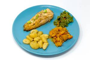 Gegrilltes Lachssteak in Hoisin-Miso Sauce´mit geschwenktem Kürbis-Zuckerschotengemüse und Gnocchi auf hellblauem Teller