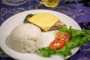 Gegrilltes Stück Fisch bedeckt mit Käse, dazu Reis zum Abendessen in Mui Ne, Vietnam