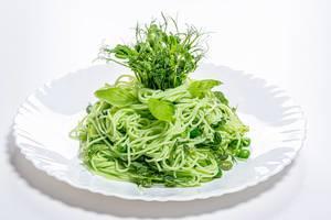 Gekochte Spaghetti mit frischen Bohnen Sprossen und jungen Bohnen auf einem weißen Teller
